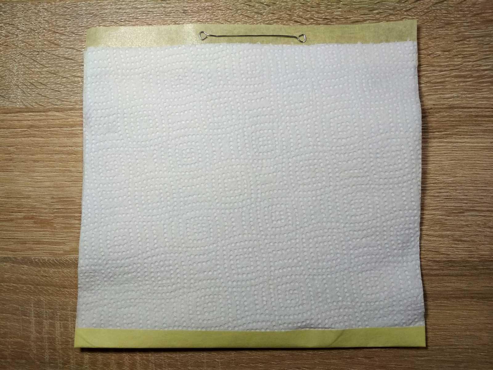 Dolną taśmą sklejamy 2 kawałki ręcznika papierowego inaklejamy elastyczny nanosek nagórną taśmę